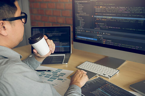 Software Engineer drinking coffee while working